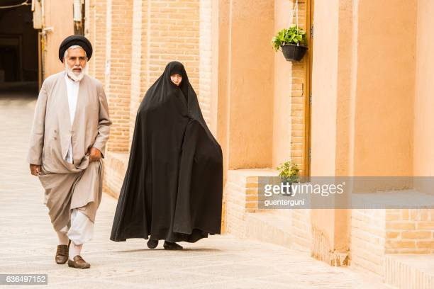 iranian couple walking in the town of yazd, iran - iran stock photos and pictures