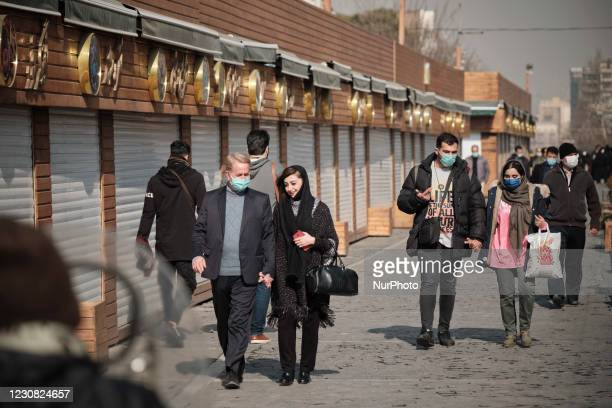 Iranian couples wearing protective face masks walk past closed fast-food shops near Tehrans Traditional Grand bazaar amid the COVID-19 outbreak in...