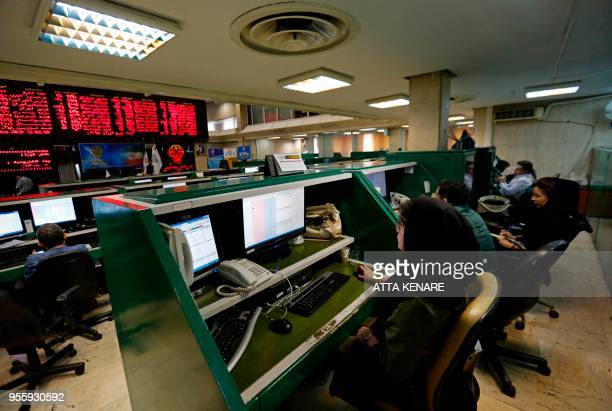 Iranian dealers monitor the stock market at the stock exchange in the capital Tehran on May 8 2018 Renewed nuclear sanctions would certainly cause...