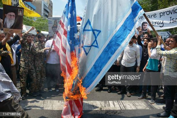 Iranian demonstrators burn a representation of the Israeli and US flag during their annual protest to mark Quds, or Jerusalem Day, in Tehran, Iran,...