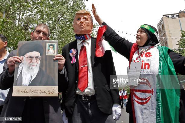 Iranian demonstrators carry a portrait of Iran's Supreme Leader Ayatollah Ali Khamenei and an effigy of US President Donald Trump during a rally in...