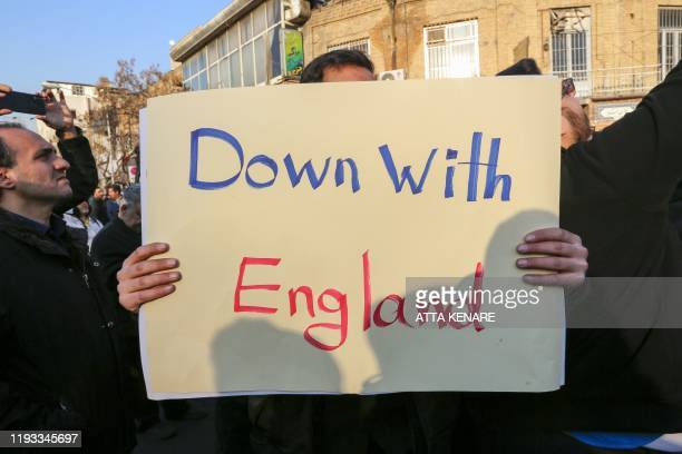 Iranian demonstrators hold placards bearing antiBritain slogans in front of the British embassy in the capital Tehran on January 12 2020 following...