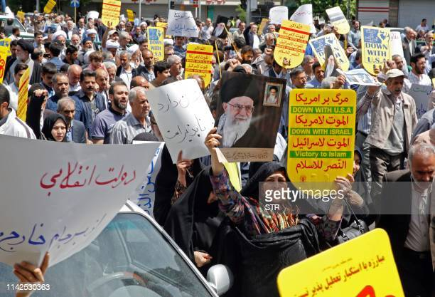 Iranian demonstrators raise placards and a portrait of Iran's Supreme Leader Ayatollah Ali Khamenei as they chant antiUS slogans during a rally in...