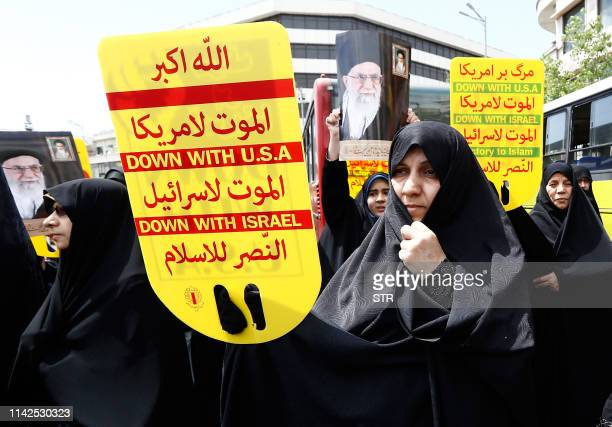 Iranian demonstrators raise placards and portraits of Iran's Supreme Leader Ayatollah Ali Khamenei as they chant antiUS slogans during a rally in the...