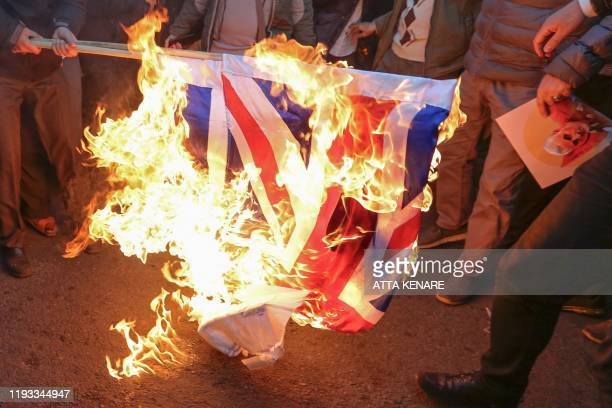 Iranian demonstrators set alight a Union Jack in front of the British embassy in Iran's capital Tehran on January 12, 2020 following the British...