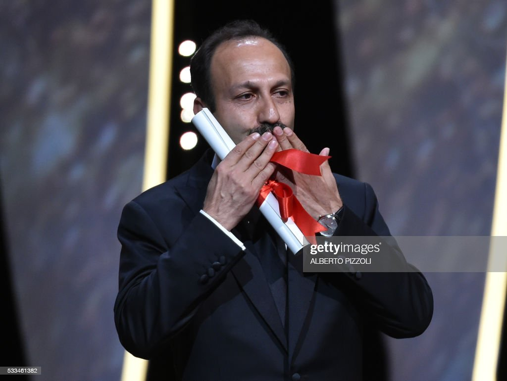 Iranian director Asghar Farhadi celebrates on stage after being awarded with the Best Screenplay prize for the film 'The Salesman (Forushande)' during the closing ceremony of the 69th Cannes Film Festival in Cannes, southern France, on May 22, 2016. /