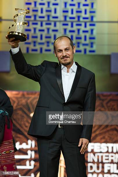"""Iranian director Vahid Vakilifara poses with the Jury Prize award for his film """"Taboor""""during the award ceremony of the 12th International Marrakech..."""