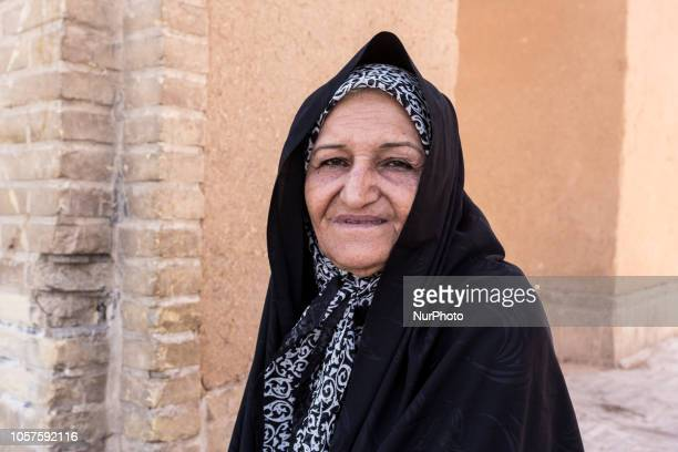 Iranian elderly woman from Balochistan region of so called Baloch people in black chador sits on a street of Yazd on September 17 2018