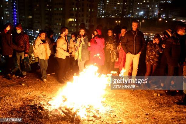 Iranian families light fire outside their houses in Tehran on March 16, 2021 during the Wednesday Fire feast, or Chaharshanbeh Soori, held annually...