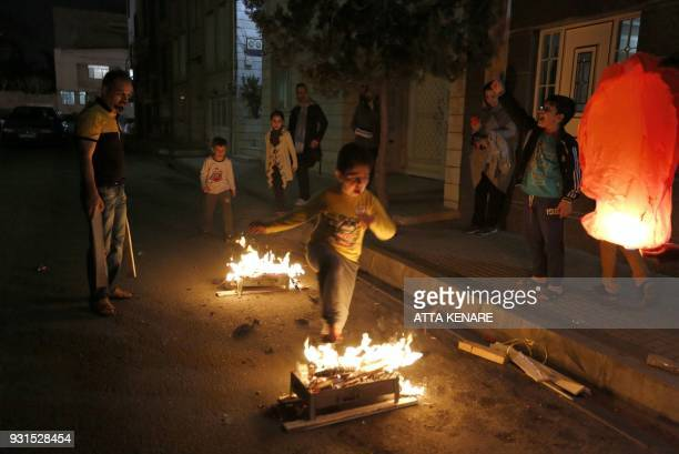 Iranian families light fire outside their houses in Tehran on March 13 2018 during the Wednesday Fire feast or Chaharshanbeh Soori held annually on...