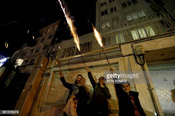 Iranian families light firecrackers outside their houses in Tehran on March 13 2018 during the Wednesday Fire feast or Chaharshanbeh Soori held...