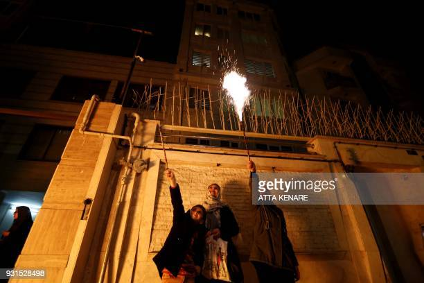 TOPSHOT Iranian families light firecrackers outside their houses in Tehran on March 13 2018 during the Wednesday Fire feast or Chaharshanbeh Soori...