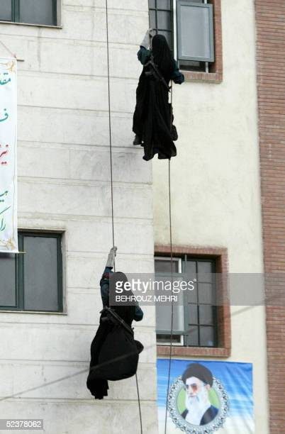 Iranian female police slide down the rope next to a portrait of Iran's supreme leader, Ayatollah Ali Khamenei during a drill for their graduation...