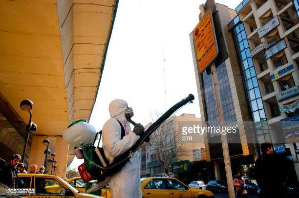 Iranian fire fighters and municipality workers disinfect a street in the capital Tehran for corona virus COVID19 on March 5 2020 Iran today reported...