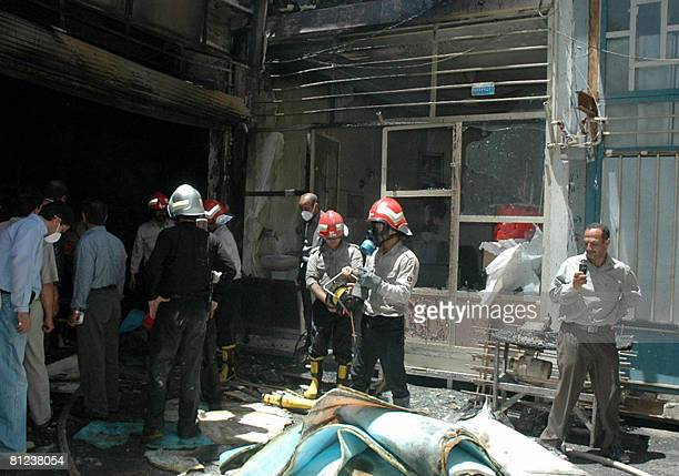 Iranian fire fighters extinguish a fire inside a furniture upholstery market in the central Iranian city of Arak on May 26 2008 No victims were...
