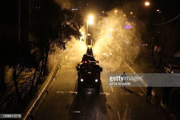 TOPSHOT Iranian firefighters disinfect streets and alleys in southern Tehran to halt the wild spread of coronavirus on March 11 2020 The novel...