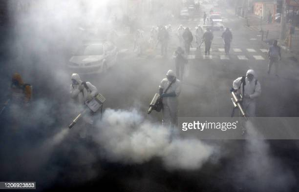 Iranian Firefighters disinfect streets in the capital Tehran in a bid to halt the wild spread of coronavirus on March 13 2020. - Iranian forces will...