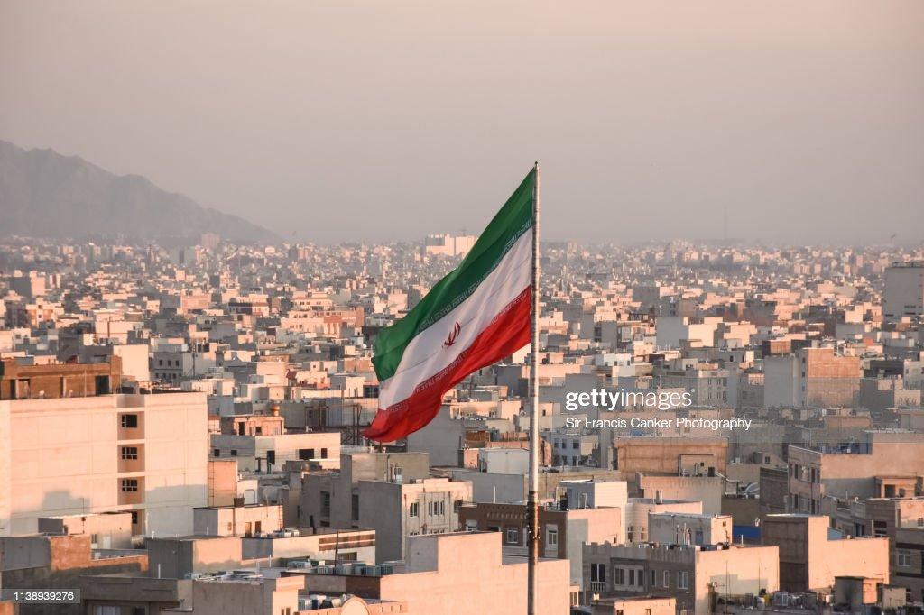 Iranian flag waving with city skyline on background in Tehran, Iran : Stock Photo