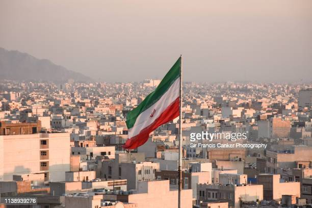 iranian flag waving with city skyline on background in tehran, iran - イラン ストックフォトと画像
