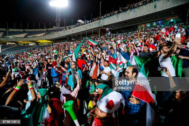 Iranian football supporters cheer for their national team during a screening of the Russia 2018 World Cup Group B football match between Iran and...