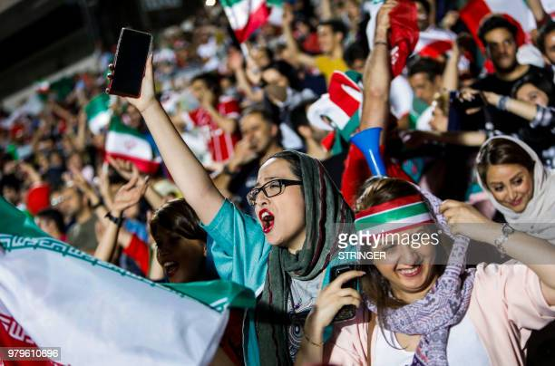 Iranian football supporters wave their national flags as they cheer for their national team during a screening of the Russia 2018 World Cup Group B...