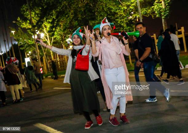 Iranian football supporters wearing the national football team's colours blow vuvuzelas outside Azadi stadium in the capital Tehran on June 20 2018...
