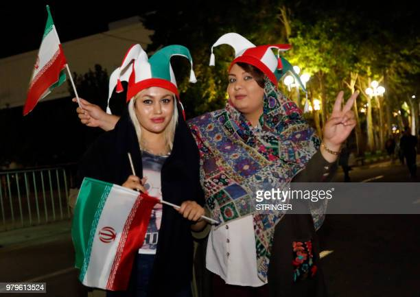 Iranian football supporters wearing the national football team's colours wave national flags outside Azadi stadium in the capital Tehran on June 20...