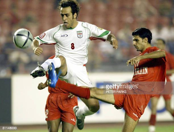 Iranian footballer Ali Karimi is tackled by Bahraini defender Hussain Baba as he scores the second goal for during the Asian Cup third place final...