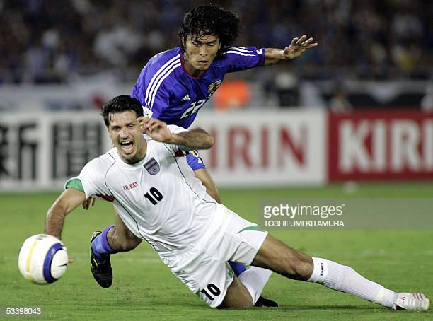 Iranian footballer and captain Ali Daei falls to get a penalty kick after he received a foul from Japanese defender Yuji Nakazawa during the second...