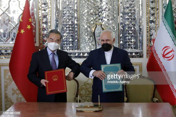 Iranian Foreign Minister Mohammad Javad Zarif and Chinese Foreign Minister Wang Yi pose for a photo after signing agreements between Iran and China...
