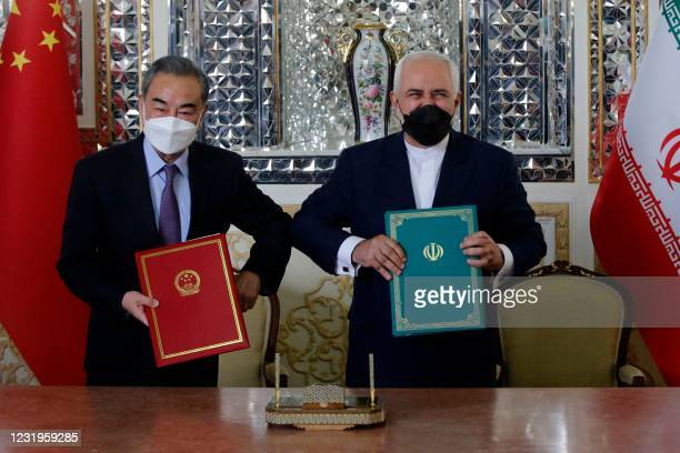 Iranian Foreign Minister Mohammad Javad Zarif and his Chinese counterpart Wang Yi, pose for a picture after signing an agreement in the capital...