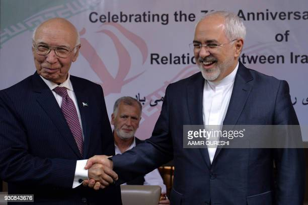 Iranian Foreign Minister Mohammad Javad Zarif shakes hands with Deputy Chairman of Pakistan's Planning Commission Sartaj Aziz during an event at the...