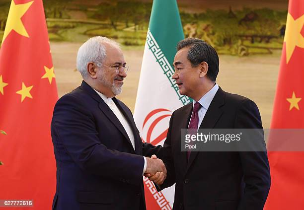 Iranian Foreign Minister Mohammad Javad Zarif shakes hands with Chinese Foreign Minister Wang Yi after a joint press conference on December 5 2016 in...