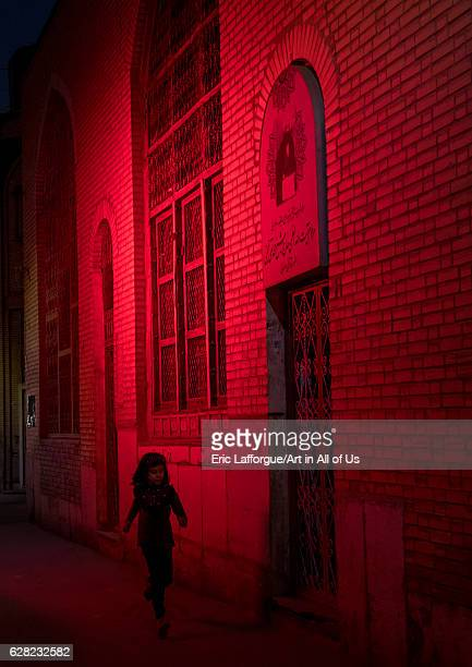 Iranian girl running in a street illuminated with red light for Muharram to commemorate the martyrdom anniversary of Hussein Isfahan Province Isfahan...
