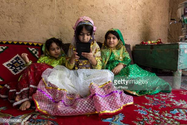 Iranian girls dressed in traditional clothes play on a mobile pad in their village home near Yazd on September 16 2018