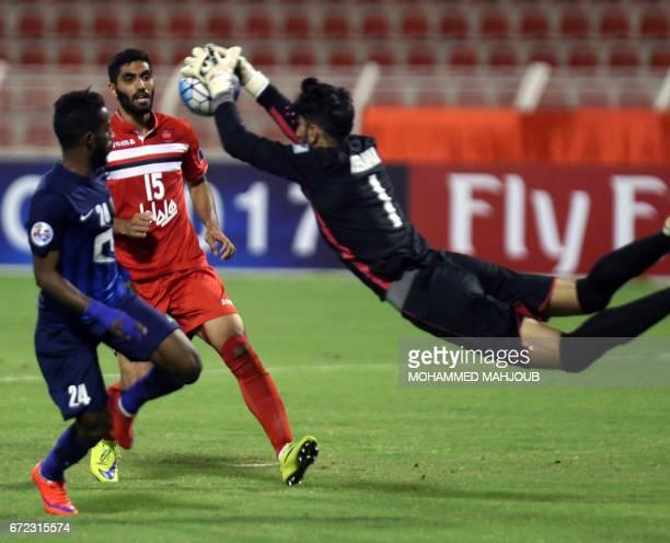 Iranian goalkeeper Alireza Beiranvand of Persepolis FC saves a shot on goal as his teammate Mohammad Ansari and Nawaf AlAbid of Saudi AlHilal FC look...