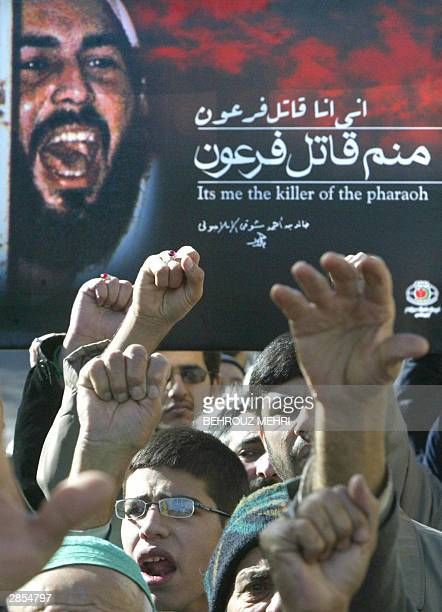 Iranian hardliners hold up a portrait of Khaled Eslamboli the assassin of former Egyptian president Anwar Sadat killed in 1981 during a military...