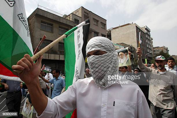 Iranian hardliners, waving Palestinian flags and portraits of the Islamic republic's supreme leader Ayatollah Ali Khamenei, protest during a rally...