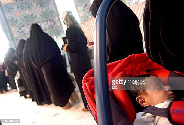 TEHRAN IRAN Iranian housewives carry their children as they stand in line at to cast their ballots in the presidential runoff between Akbar Hashemi...
