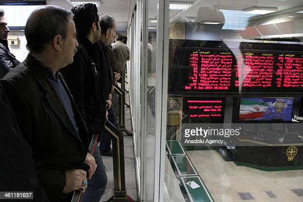 Iranian investors watch the prices of shares at the Tehran Stock Exchange after the banks reduced the profit share rates and Iran controlled the...