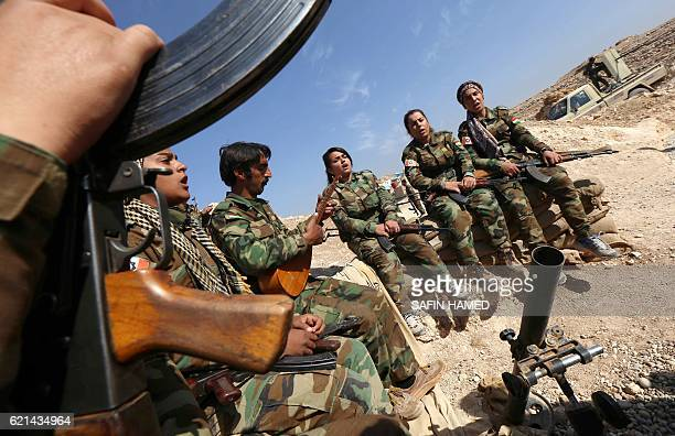 Iranian Kurdish female members of the Freedom Party of Kurdistan listen to a musician and sing as they hold a position on November 6 2016 in an area...