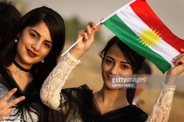 Iranian Kurdish girls hold a Kurdish flag and flash the sign for victory as they take part in a gathering to urge people to vote in the upcoming...