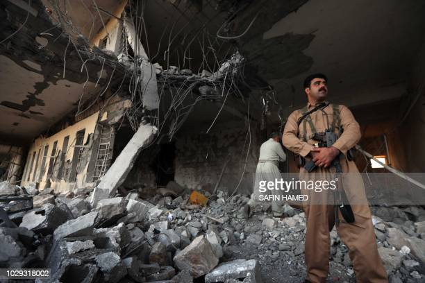 Iranian Kurdish Peshmerga members of the Iranian Kurdistan Democratic Party check the damage after a rocket attack inside their headquarters in...