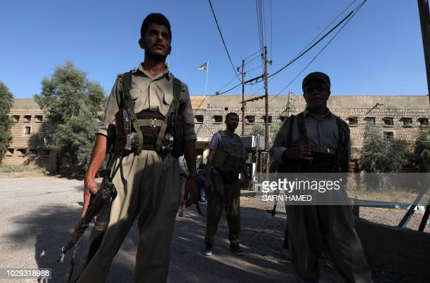 Iranian Kurdish Peshmerga members of the Iranian Kurdistan Democratic Party stand guard by their headquarters after a rocket attack in Koysinjaq 100...