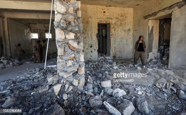 Iranian Kurdish Peshmerga members of the Kurdistan Democratic Party of Iran inspect damage at their party headquarters in Koysinjaq 100 kilometres...