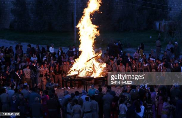 Iranian Kurdish Peshmerga members of the Kurdistan Democratic Party of light a bonfire as they celebrate Noruz the Persian New Year in the town of...