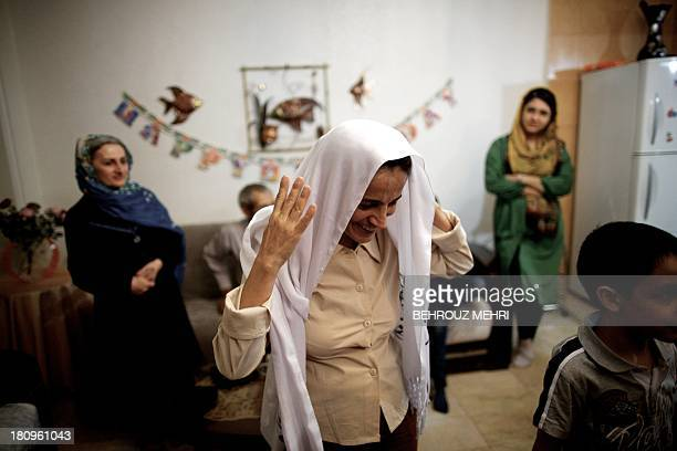 Iranian lawyer Nasrin Sotoudeh puts on her scarf as she welcomes her guests at her house in Tehran on September 18 after being freed after three...