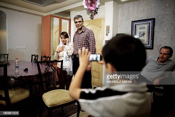 Iranian lawyer Nasrin Sotoudeh speaks on the phone next to her husband Reza Khandan as their son Nima takes their picture at her house in Tehran on...