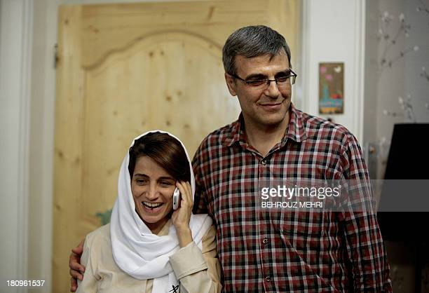 Iranian lawyer Nasrin Sotoudeh speaks on the phone next to her husband Reza Khandan as they pose for a photo at their house in Tehran on September 18...