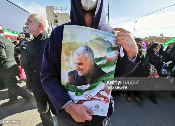 A Iranian man carries a portrait of slain Iranian General Qasem Soleimani on the 40th day of his killing in a US drone strike during commemorations...